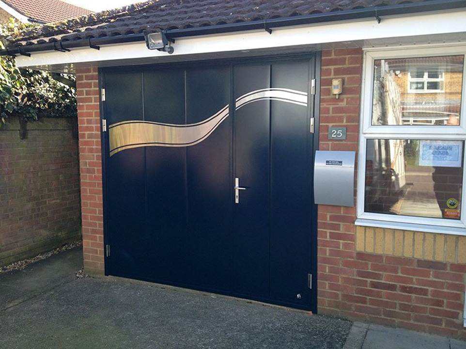 Side hinged garage door with stainless steel applique